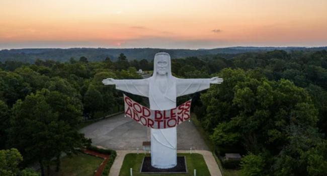 Lo striscione blasfemo delle femministe pro aborto sulla statua del Cristo in Arkansas